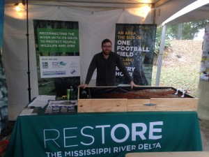 Philip Russo shows off with the Restore the Mississippi River Delta coalition's diversion model at the Plaquemines Orange Festival.