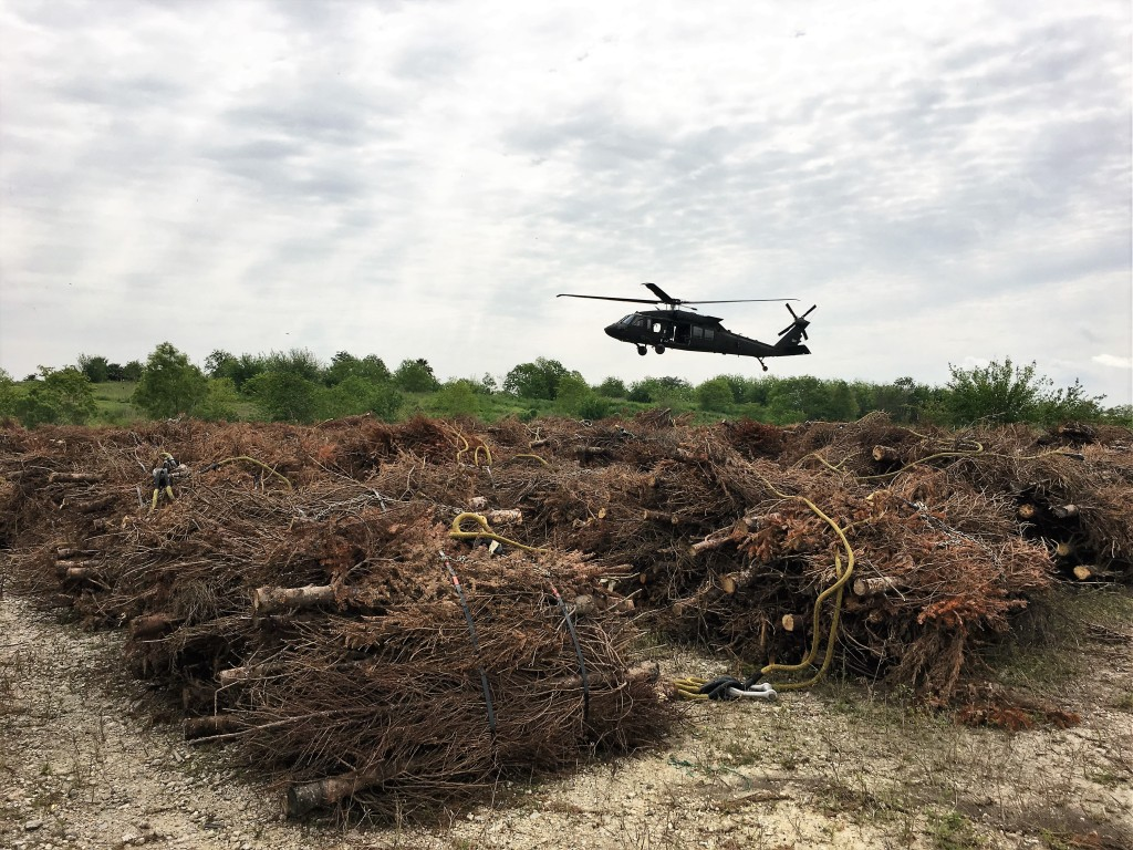 Blackhawk Helicopter picks up a bundle of Christmas trees.