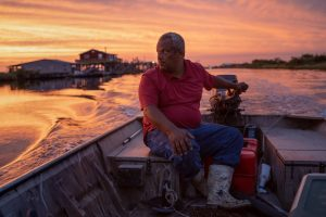 Gleason Alexis, a shrimper, drives his boat at sunset.